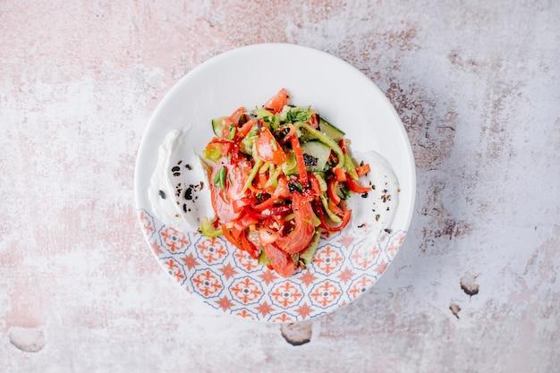 Ensalada mixta de verduras con pimientos de colores dentro de la placa decorativa.
