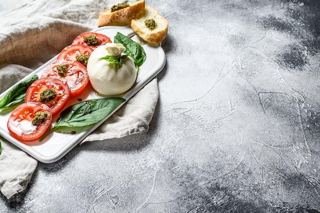 Ensalada de mozzarella burrata con hojas de albahaca y tomates. fondo gris vista superior. espacio para texto