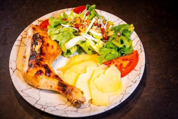 Ensalada de muslo de pollo y ensalada sobre un fondo negro, sobre una placa blanca.