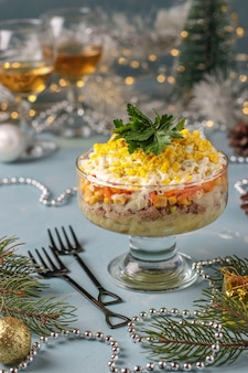 Ensalada navideña con conservas de pescado, huevos, zanahorias y patatas, comida tradicional rusa, primer plano, orientación vertical