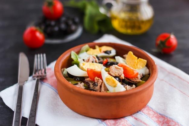 Ensalada nicoise con atún, judías verdes, albahaca y verduras frescas.