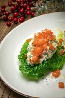 Ensalada olivier con salmón en una mesa de madera
