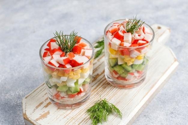 Ensalada con palitos de cangrejo, huevos, maíz y pepino.