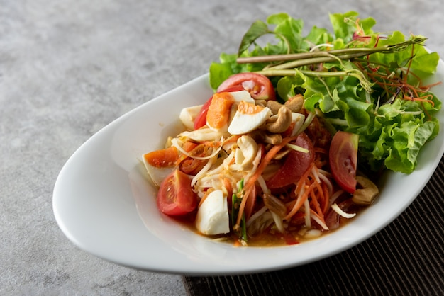 Ensalada de papaya con huevos salados en un plato, ensalada somtum o papaya tailandesa