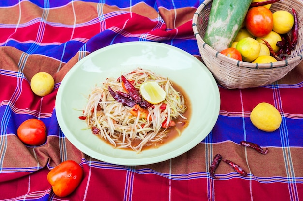 Ensalada de papaya en plato e ingredientes, arroz pegajoso en fondo de taparrabos
