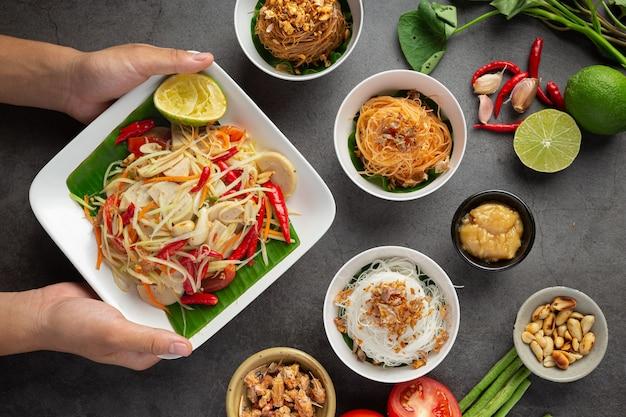 Ensalada de papaya servida con fideos de arroz y ensalada de verduras decorada con ingredientes de la comida tailandesa.