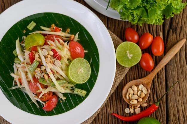 Ensalada de papaya (som tum thai) en un plato blanco sobre una mesa de madera.