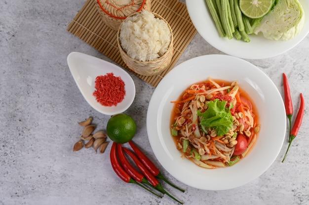 Ensalada de papaya tailandesa en un plato blanco con arroz en cesta de mimbre de bambú y camarones secos