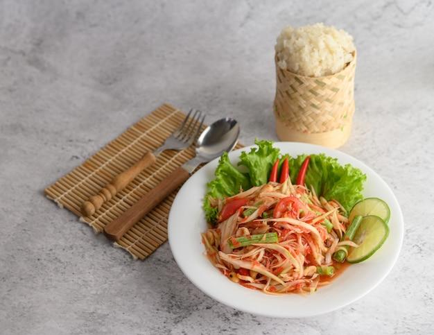 Ensalada de papaya tailandesa en un plato blanco con arroz pegajoso