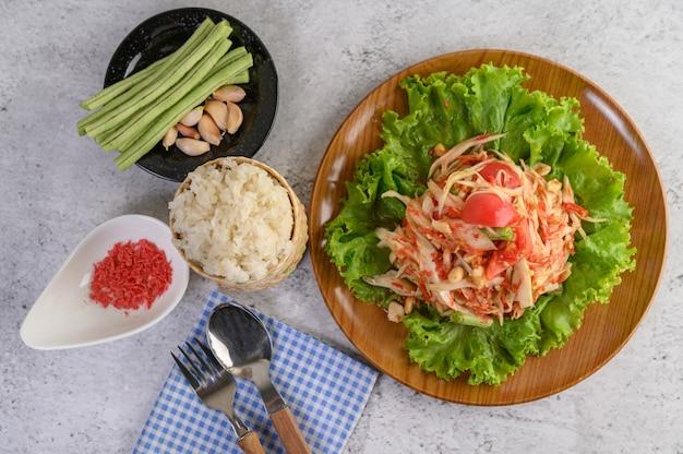 Ensalada de papaya tailandesa en un plato de madera con arroz pegajoso