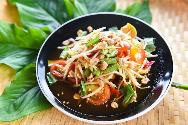 Ensalada de papaya verde comida tailandesa picante en la hoja verde