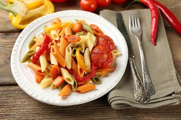 Ensalada de pasta con pimiento, zanahoria y tomate en mesa de madera
