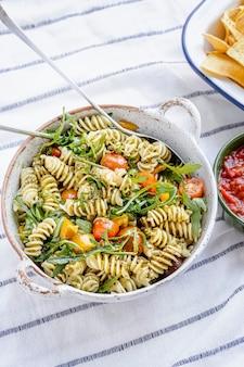 Ensalada de pasta rotini con rúcula y tomates cherry, plato de verano saludable