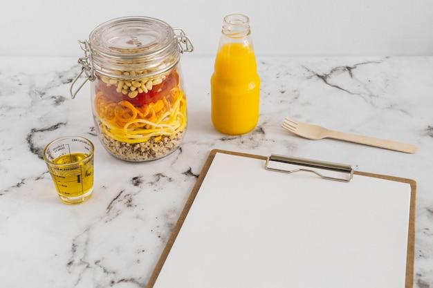 Ensalada de pasta en tarro con aceite; jugo; portapapeles y tenedor en superficie de mármol