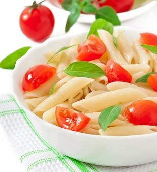Ensalada de pasta con tomates cherry y hojas frescas de albahaca