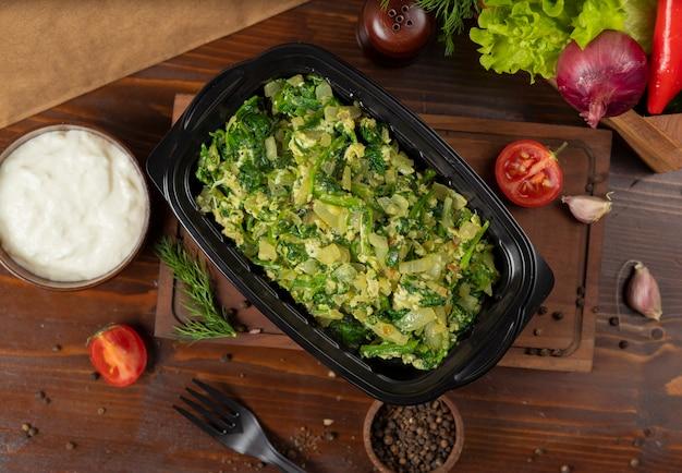 Ensalada de patata con huevos, hierbas y verduras picadas.