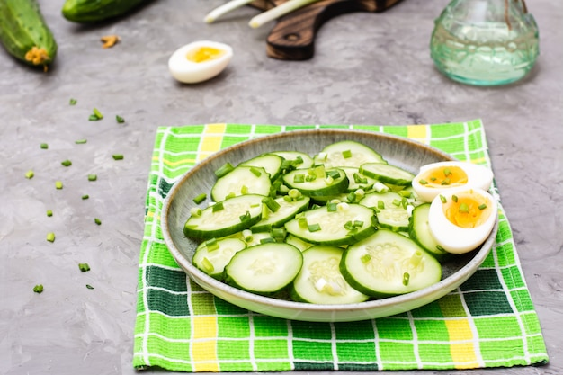 Ensalada de pepino fresco, huevos de gallina hervida y cebolla verde en un plato sobre la mesa