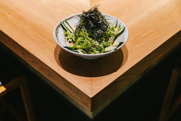 Ensalada de pepino japonés con lechuga, rábano y algas secas servido en un tazón de cerámica sobre mostrador de madera.