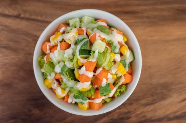 Ensalada de pepino, maíz, zanahoria y lechuga en una taza blanca.