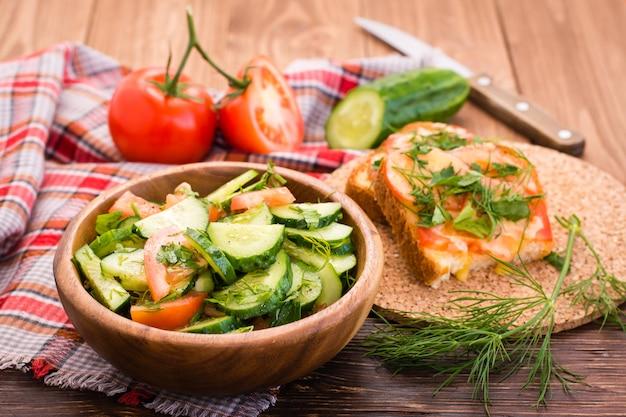 Ensalada de pepinos y tomates en un plato de madera, sándwiches horneados con queso y verduras sobre la mesa