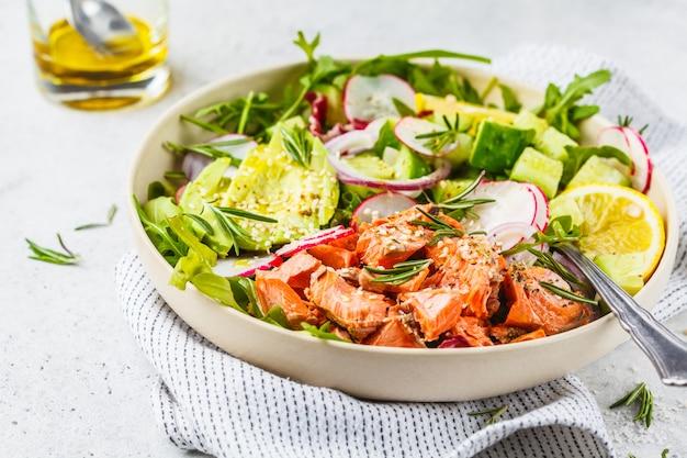 Ensalada de pescado rojo al horno con aguacate, pepino, rábano y rúcula en un plato blanco.