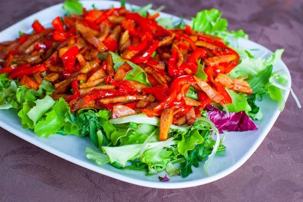 Ensalada picada con pimientos, lechuga y tomates en un plato blanco sobre la mesa