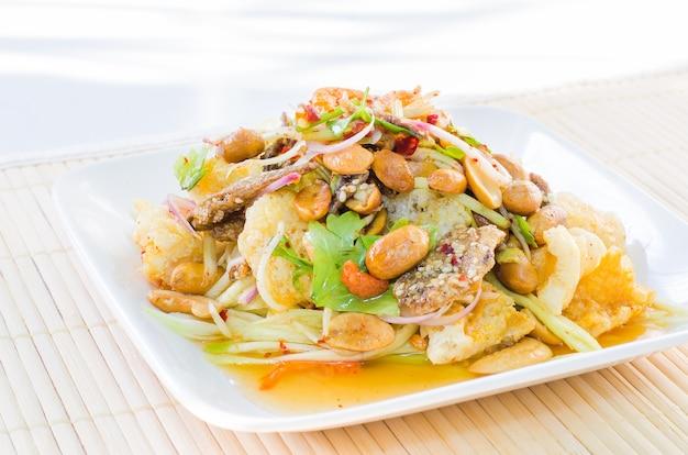 Ensalada picante y amarga tailandesa con pescado crujiente y nueces en plato blanco