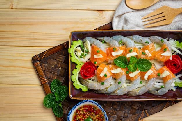 Ensalada picante de camarones y salmón sobre superficie de madera