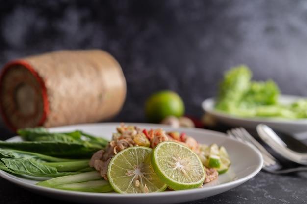 Ensalada picante de lima y cerdo con col rizada, galanga, chile y ajo en un plato blanco sobre un piso de cemento negro.
