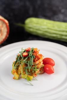 Ensalada picante de lima y cerdo con melón amargo, galanga, chile, tomate y ajo en un plato blanco sobre un piso de cemento negro.