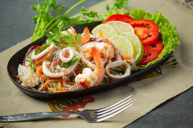 Ensalada picante de mariscos mixtos con ingredientes de comida tailandesa.