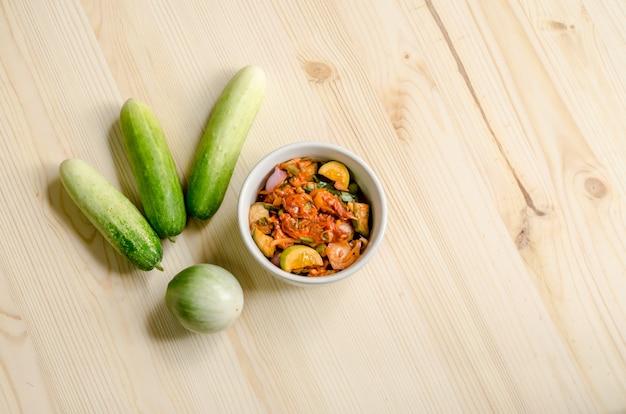 Ensalada picante de los mejillones conservados en vinagre con el pepino y la berenjena tailandesa en la tabla de madera, comida tailandesa.