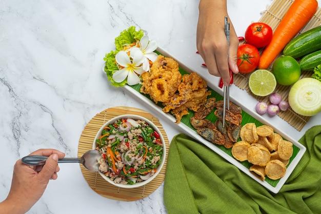 Ensalada picante mixta con salchicha vietnamita, huevo en conserva y calamar crujiente, comida tailandesa.