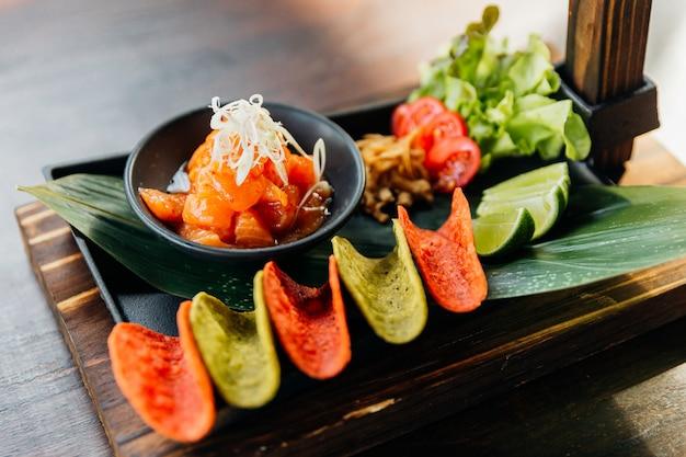 Ensalada picante de salmón crudo servido con chips crujientes rojos y verdes para canapé.