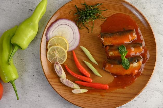 Ensalada picante de sardina en salsa de tomate en bandeja de madera