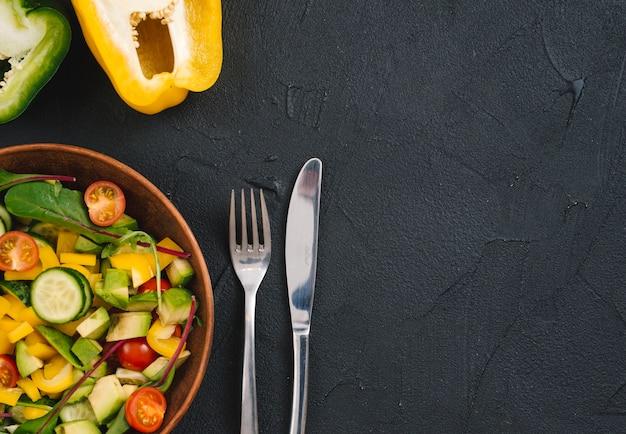 Ensalada de pimientos a la mitad y verduras mixtas con cubiertos sobre fondo de hormigón negro