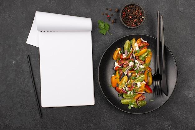 Ensalada plana de tomate con queso feta, rúcula y bloc de notas en blanco