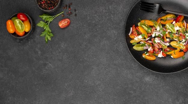 Ensalada plana de tomate con queso feta, rúcula y espacio de copia