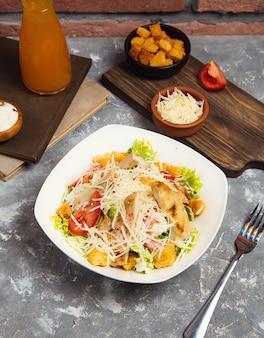Ensalada de pollo. ensalada césar de pollo. ensalada césar con pollo a la parrilla en un plato. pechugas de pollo a la plancha y ensalada fresca en placa.