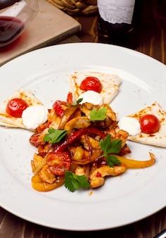Ensalada de pollo fresca con la preparación vegetal, pan caucásico árabe en una placa blanca. menú dietético. nutrición apropiada.