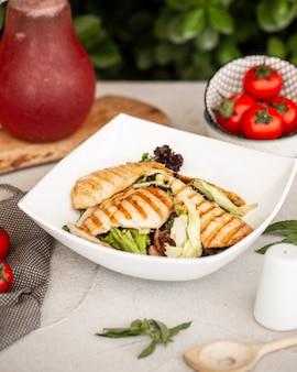Ensalada de pollo con lechuga y maíz en tazón de cerámica blanca