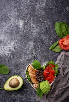 Ensalada con pollo, quinoa negra, tomates y aguacate en el recipiente en forma de corazón. balance saludable