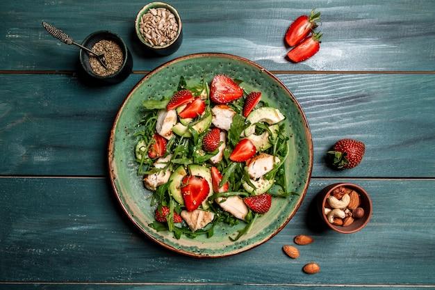 Ensalada de pollo con rúcula, aguacate y fresas. plato con comida de dieta cetogénica. vista superior