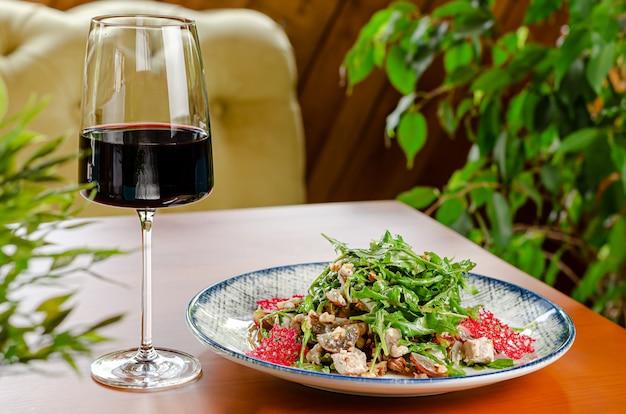 Ensalada de pollo con rúcula y nueces aderezo servido con una copa de vino tinto en la mesa de madera. copia espacio