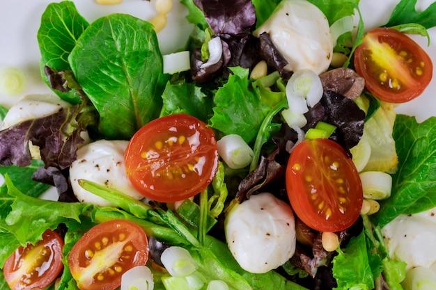 Ensalada de primavera con tomate cherry, mozzarella y aceite de oliva en un plato