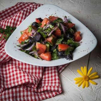 Ensalada de primer plano con tomate, pepino, lechuga, cebolla, aceitunas en un mantel de plato blanco