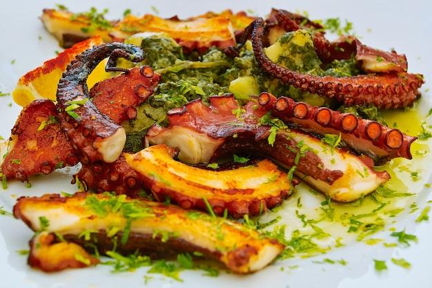 Ensalada de pulpo caliente con verduras salteadas en la placa blanca.