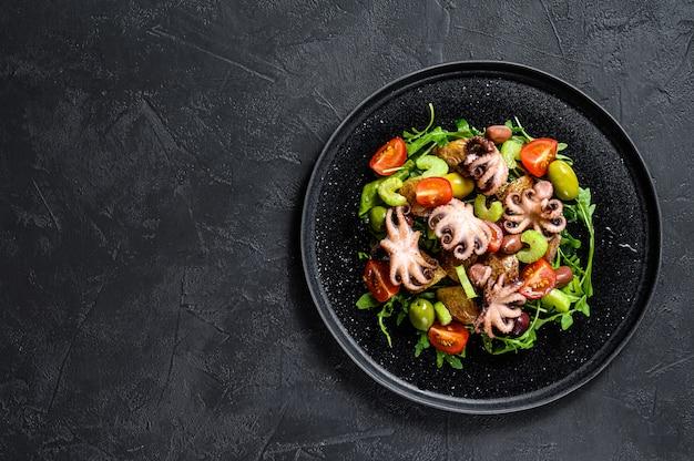 Ensalada con pulpo a la parrilla, papas, rúcula, tomates y aceitunas. fondo negro. vista superior. copyspace