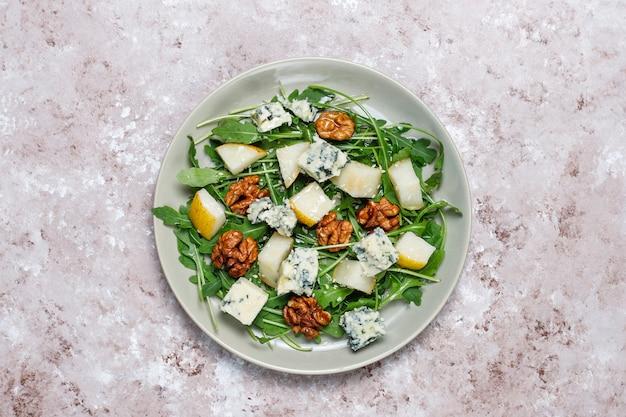 Ensalada de queso azul con nuez y ruccola y aceite de oliva y rodajas de pera