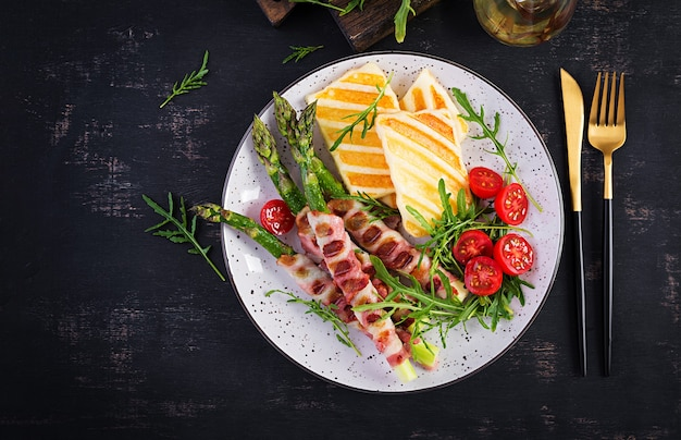 Ensalada de queso halloumi a la parrilla con tomates y espárragos en tiras de tocino en un plato sobre fondo oscuro. comida sana. vista superior, arriba